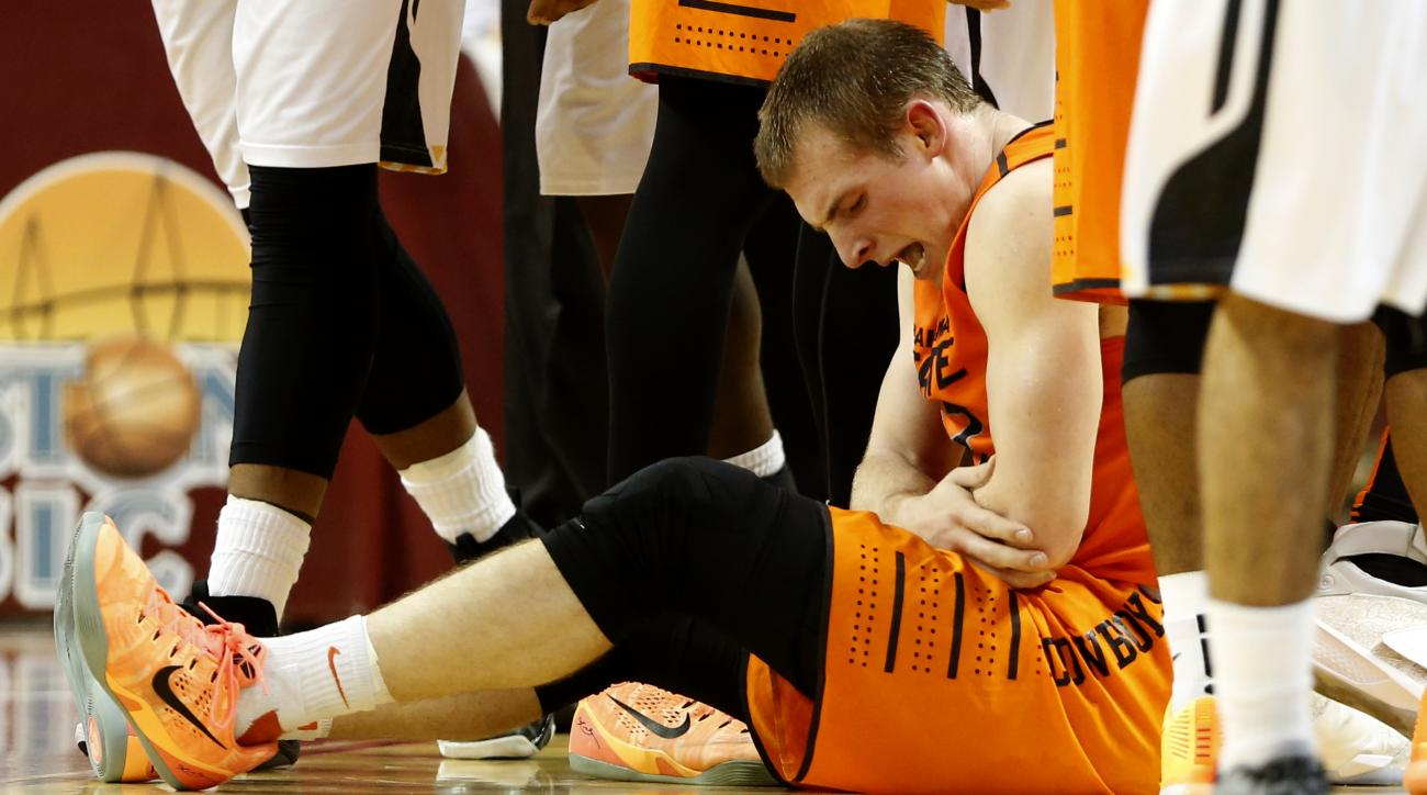 Oklahoma State's Phil Forte, III, holds his injured elbow during the first half an NCAA college basketball game against Towson at the Charleston Classic at TD Arena, Thursday Nov. 19, 2015, in Charleston, S.C. Forte tried to play the second half but came