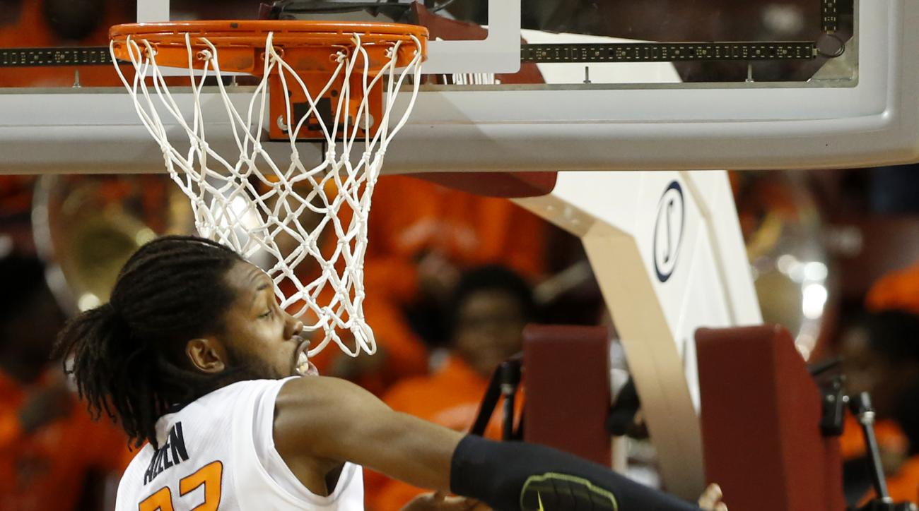 Oklahoma State's Anthony Allen Jr. (32) blocks the shot of George Mason's Jalen Jenkins (31) during the first half an NCAA college basketball game at the Charleston Classic at TD Arena, Friday Nov. 20, 2015, in Charleston, S.C. In back is Oklahoma State's