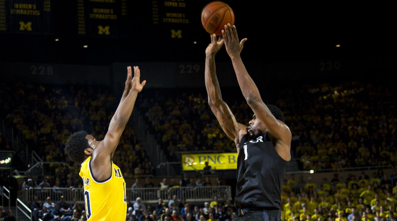 Michigan guard Derrick Walton Jr., left, defends against a shot by Xavier forward Jalen Reynolds (1) in the first half of an NCAA college basketball game at Crisler Center in Ann Arbor, Mich., Friday, Nov. 20, 2015. (AP Photo/Tony Ding)