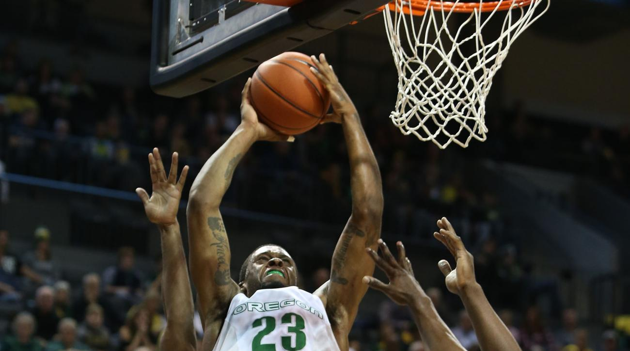 Oregon's Elgin Cook, center, goes up for a shot against Savannah State's Troyce Manassa, left, and Lenjo Kilo during the second half of an NCAA college basketball game Friday, Nov. 20, 2015, in Eugene, Ore. Oregon won 77-59. (AP Photo/Chris Pietsch)