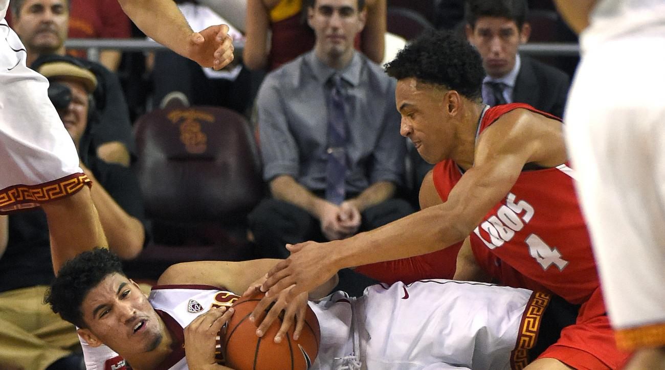 Southern California forward Bennie Boatwright, left, and New Mexico guard Elijah Brown vie for a loose ball during the first half of an NCAA college basketball game, Saturday, Nov. 21, 2015, in Los Angeles. (AP Photo/Mark J. Terrill)