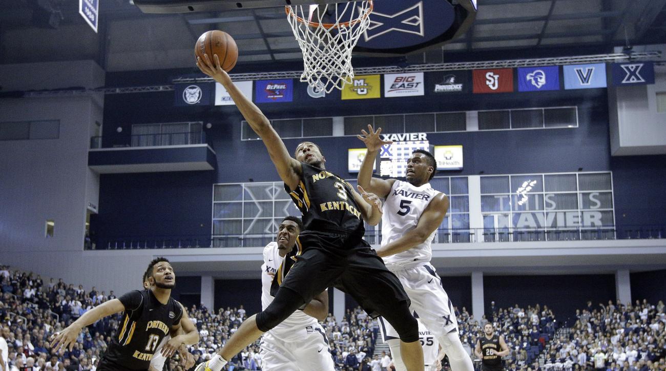 Northern Kentucky's Tyler White (3) shoots against Xavier's Trevon Bluiett (5) and James Farr, center left, as Brennan Gillis (13) looks on in the first half of an NCAA college basketball game Monday, Nov. 23, 2015, in Cincinnati. (AP Photo/John Minchillo