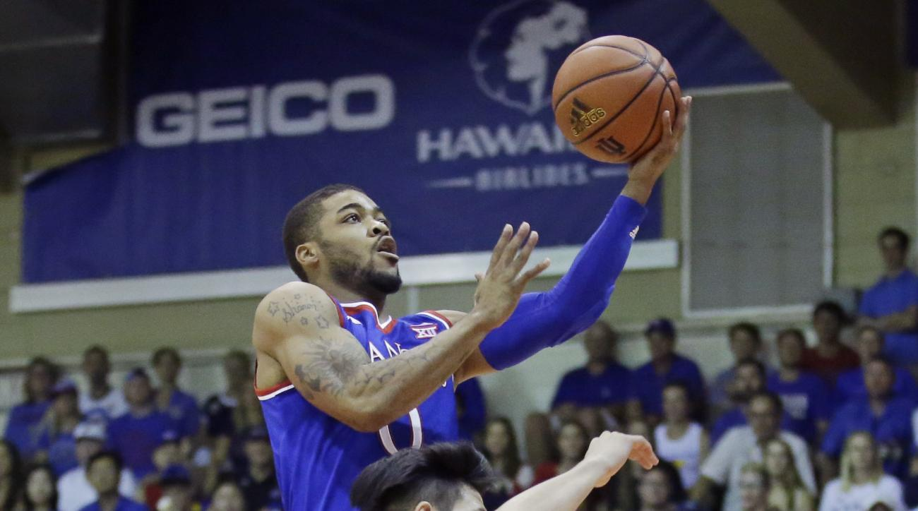 Kansas guard Frank Mason III (0) goes to the basket as Chaminade guard Kevin Hu (23) defends in the first half during an NCAA college basketball game in the first round of the Maui Invitational, Monday, Nov. 23, 2015, in Lahaina, Hawaii. (AP Photo/Rick Bo