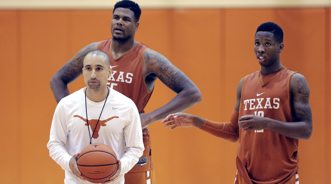 FILE - In this Oct. 13, 2015, file photo, Texas head basketball coach Shaka Smart runs drills during a practice at the team's facility as Cameron Ridley (55) and Kerwin Roach, Jr., right, look on, in Austin, Texas.No one had to explain to Texas coach Shak