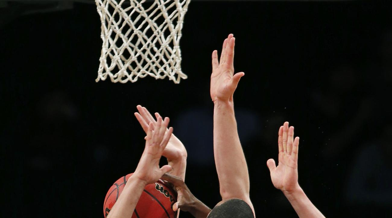 Marquette forwards Sandy Cohen III (5) and Henry Ellenson, second from right, defend Arizona State forward Willie Atwood (2) beneath ASU's basket in overtime of an NCAA college basketball game in the Legends Classic championship, Tuesday, Nov. 24, 2015, i