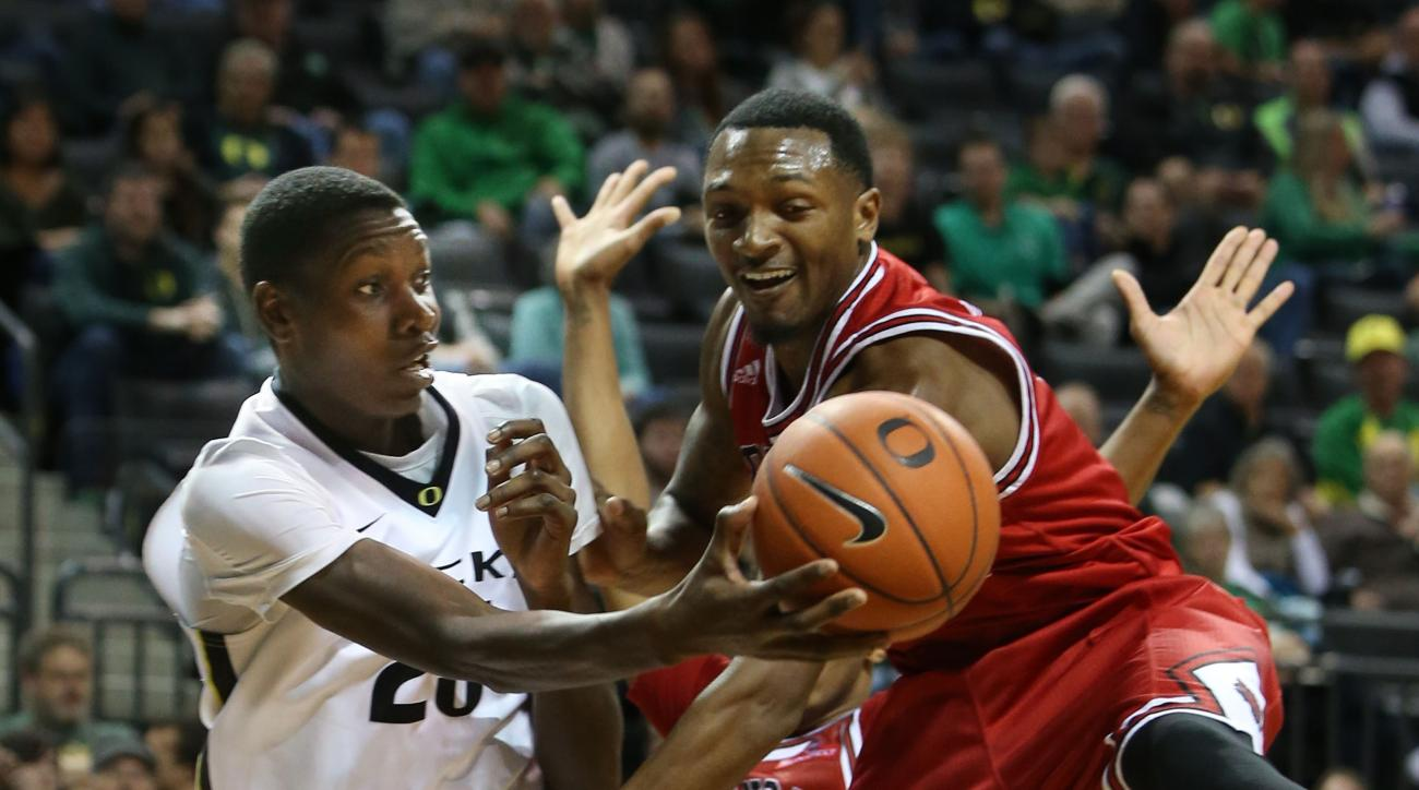Oregon's Chris Boucher, left, passes the ball out under pressure from Arkansas State's Charles Waters during the second half of an NCAA college basketball game Wednesday, Nov. 25, 2015, in Eugene, Ore. (AP Photo/Chris Pietsch)