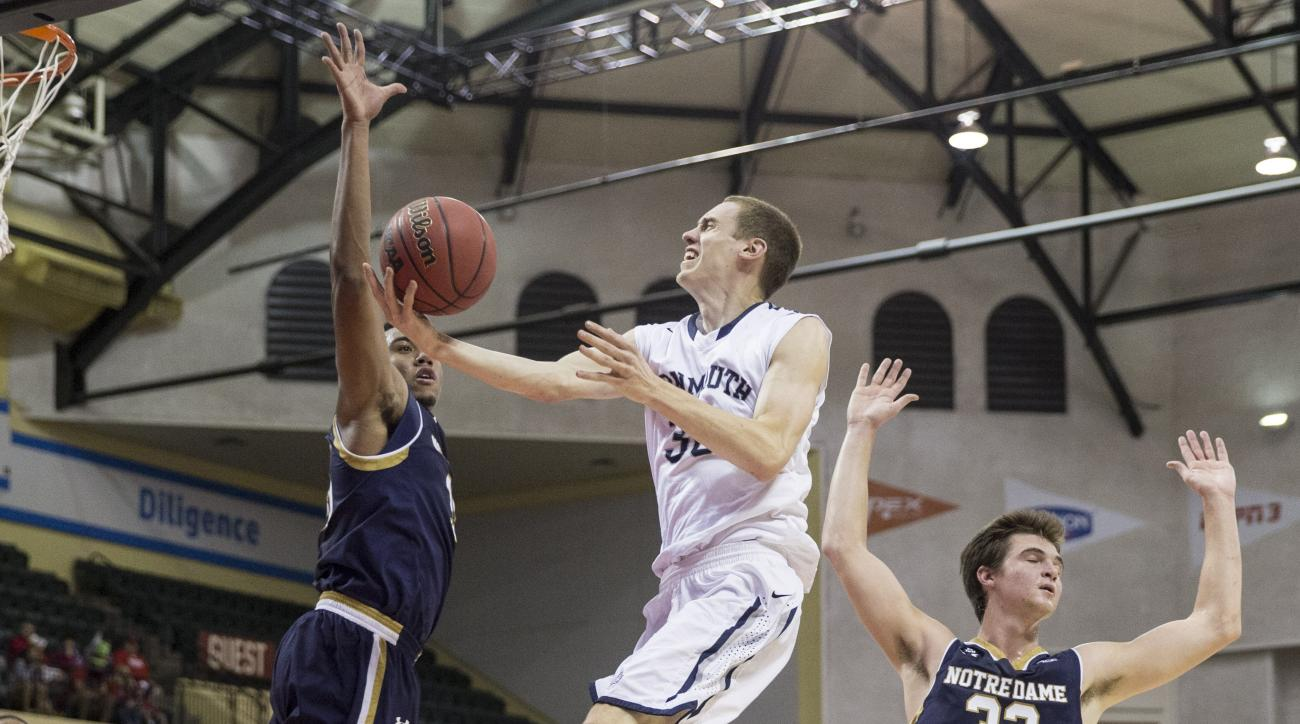 Monmouth guard Collin Stewart (30) drives to the basket as Notre Dame forward Bonzie Colson (35) and guard Steve Vasturia (32) defend during the first half of an NCAA college basketball game Thursday, Nov. 26, 2015, in Orlando, Fla. (AP Photo/Willie J. Al