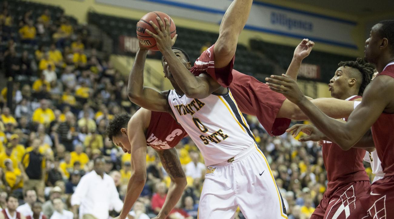 Wichita State forward Rashard Kelly (0) pulls down a rebound while Alabama forward Michael Kessens (3) goes crashing over the top of him during the first half of an NCAA college basketball game Friday, Nov. 27, 2015, in Orlando, Fla. (AP Photo/Willie J. A