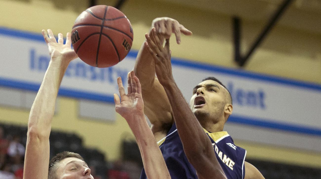 Iowa forward Jarrod Uthoff (20) has his shot blocked by Notre Dame forward Austin Torres, top, and forward V.J. Beachem (3) during the first half of an NCAA college basketball game Friday, Nov. 27, 2015, in Orlando, Fla. (AP Photo/Willie J. Allen Jr.)