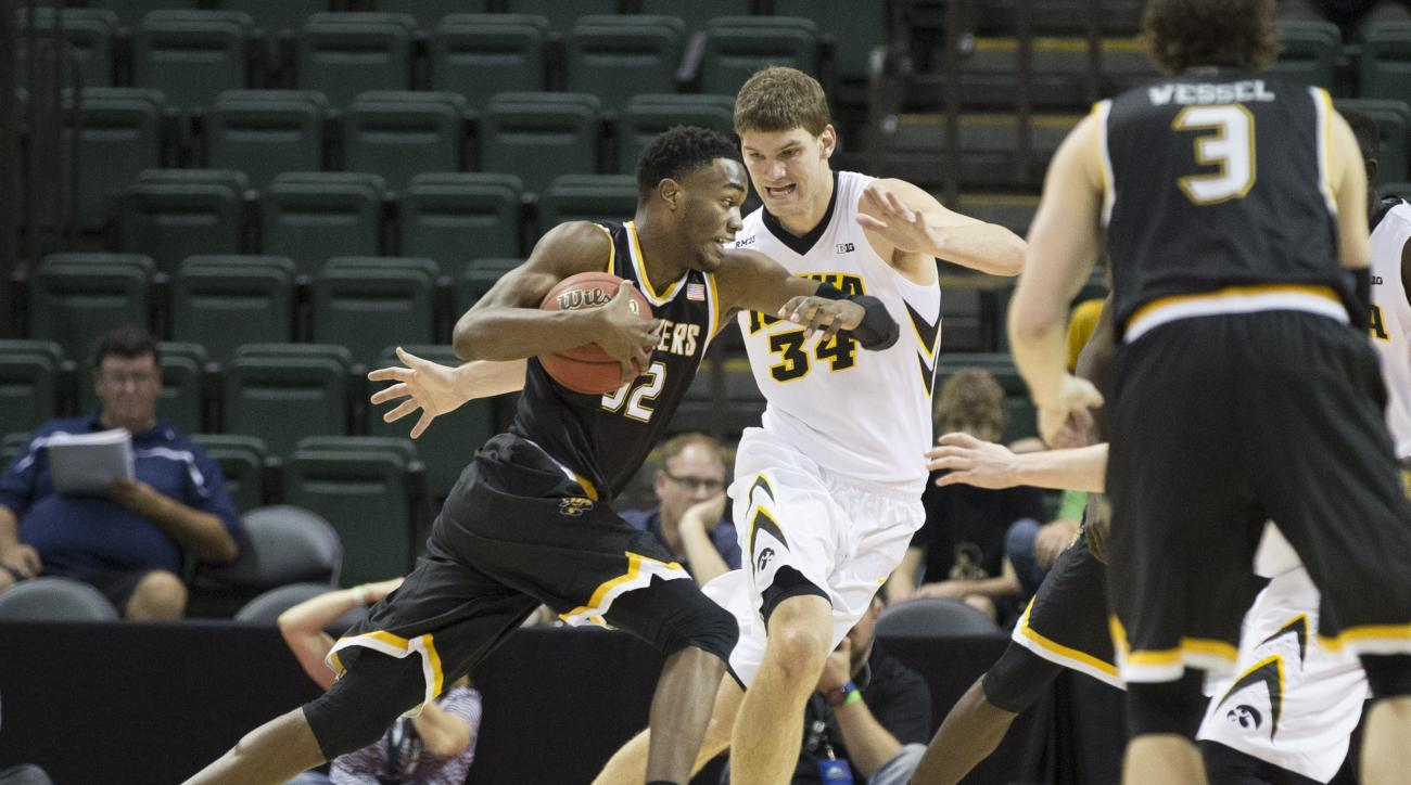 Wichita State forward Markis McDuffie (32) dribbles the ball against Iowa center Adam Woodbury (34) during the first half of an NCAA college basketball game Sunday, Nov. 29, 2015, in Orlando, Fla. (AP Photo/Willie J. Allen Jr.)