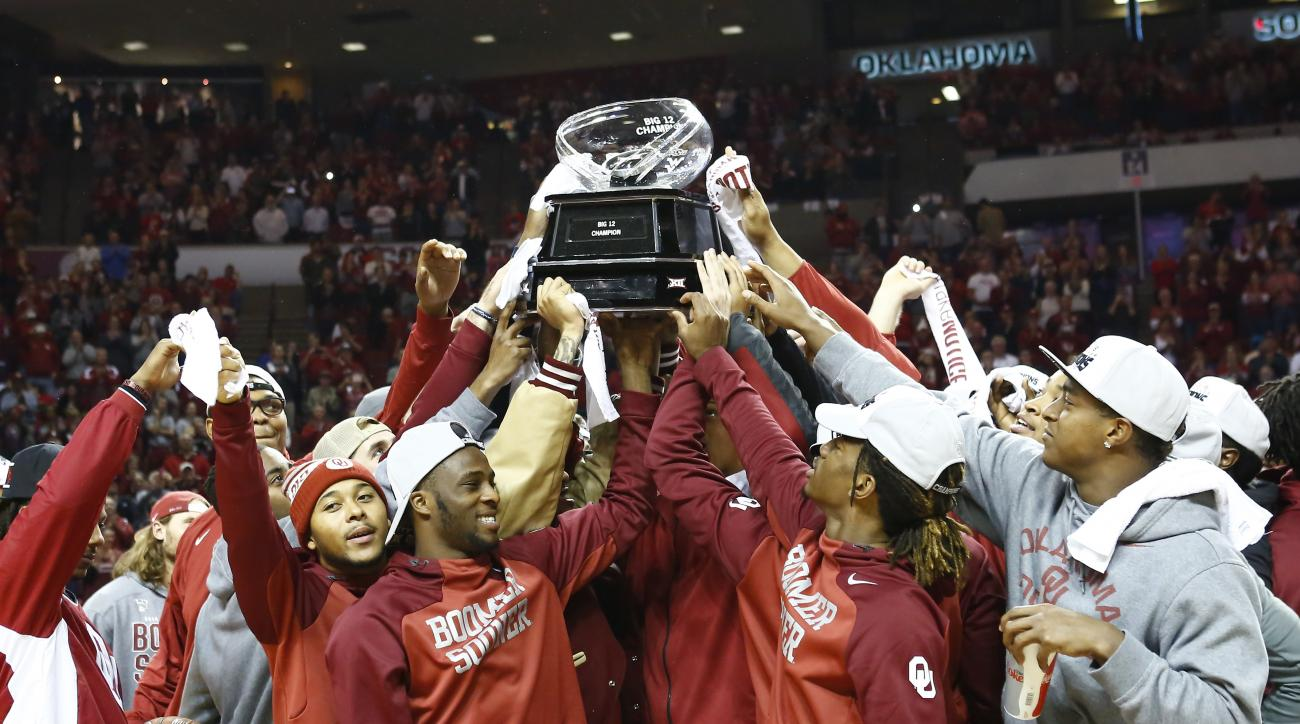 The Oklahoma Football team holds up their 2015 Big 12 Trophy during halftime of an NCAA college basketball game against Wisconsin in Norman, Okla., Sunday, Nov. 29, 2015. (AP Photo/Alonzo Adams)