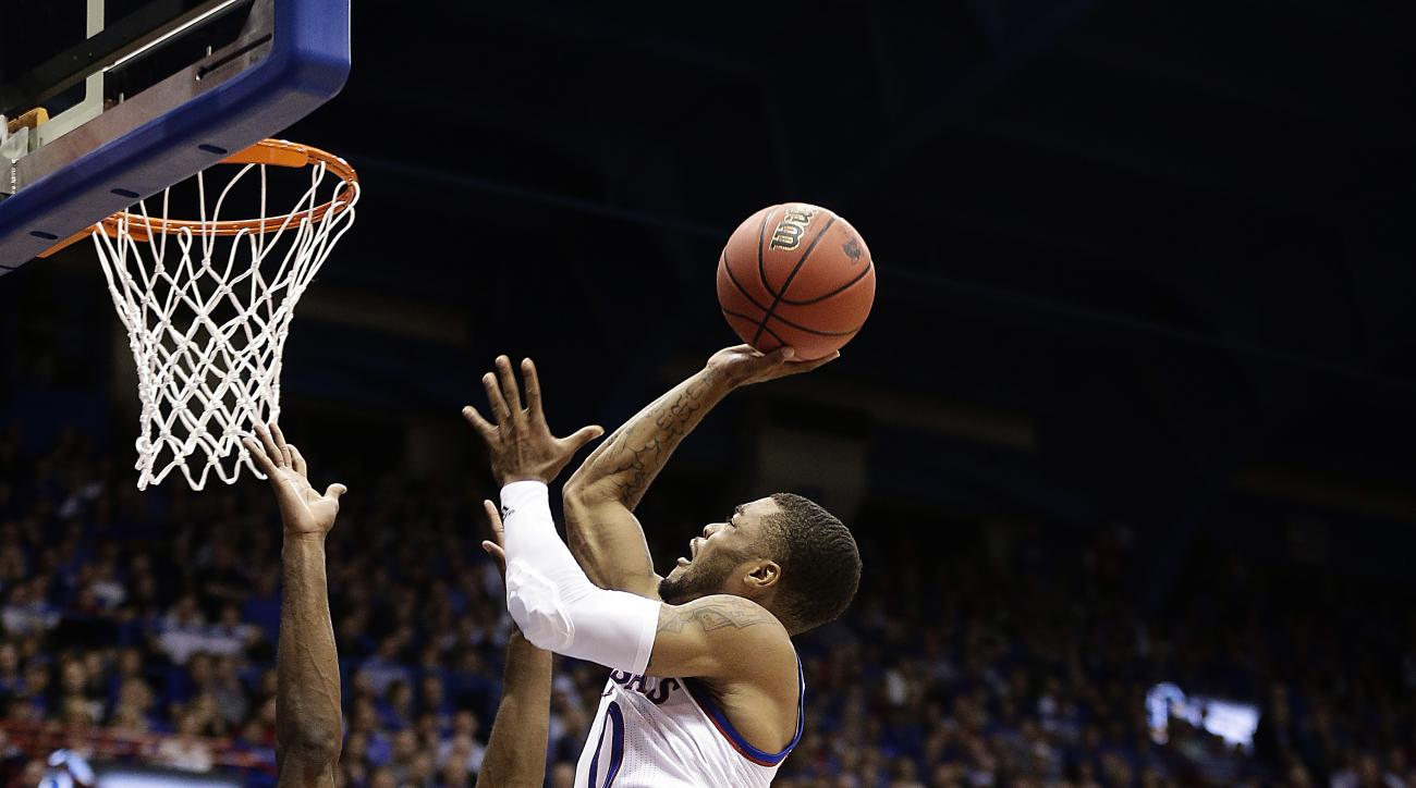 Kansas' Frank Mason III (0) gets past Loyola's Eric Laster (5) to put up a shot during the first half of an NCAA college basketball game Tuesday, Dec. 1, 2015, in Lawrence, Kan. (AP Photo/Charlie Riedel)