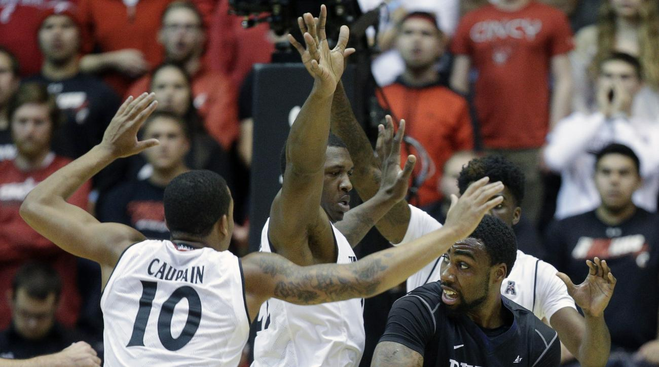 Butler's Roosevelt Jones (21) looks to pass around Cincinnati's Coreontae DeBerry, center, and Troy Caupain (10) in the first half of an NCAA college basketball game, Wednesday, Dec. 2, 2015, in Cincinnati. (AP Photo/John Minchillo)