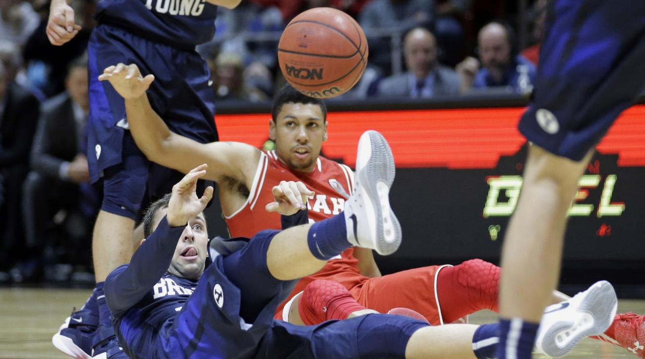 BYU guard Nick Emery, left, passes the ball as Utah forward Jordan Loveridge, rear, looks on in the second half during an NCAA college basketball game Wednesday, Dec. 2, 2015, in Salt Lake City. (AP Photo/Rick Bowmer)