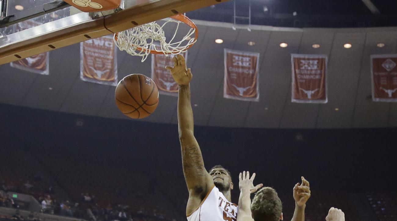 Texas center Cameron Ridley, center, scores over Samford forward Alex Peters (55) during the second half of an NCAA college basketball game Friday, Dec. 4, 2015, in Austin, Texas. Texas won 59-49. (AP Photo/Eric Gay)