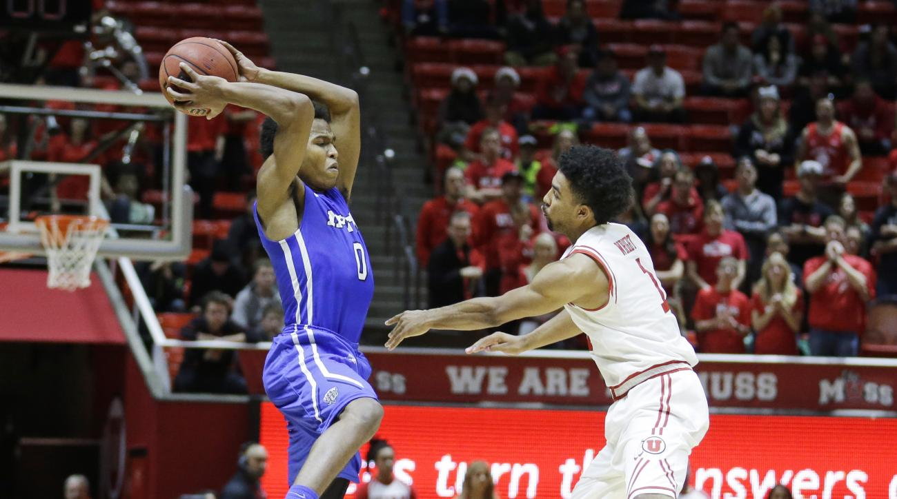 IPFW's Mo Evans (0) catches a pass as Utah guard Isaiah Wright (1) defends in the first half during an NCAA college basketball game Saturday, Dec. 5, 2015, in Salt Lake City. (AP Photo/Rick Bowmer)