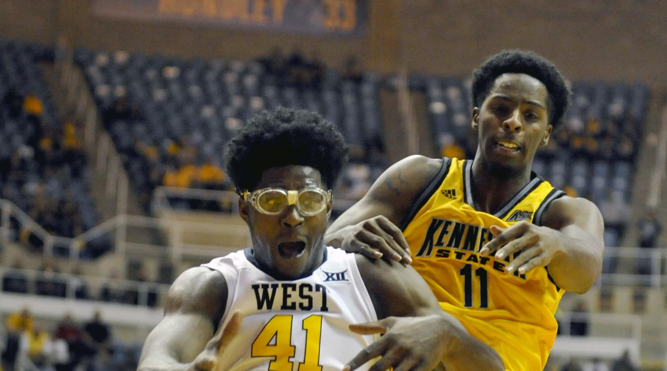 West Virginia's Devin Williams (41) fights Kennesaw State's Kyle Hector (11) for a rebound during an NCAA college basketball game in Morgantown, W. Va., Saturday, Dec. 5, 2015. (AP Photo/Chris Tilley)