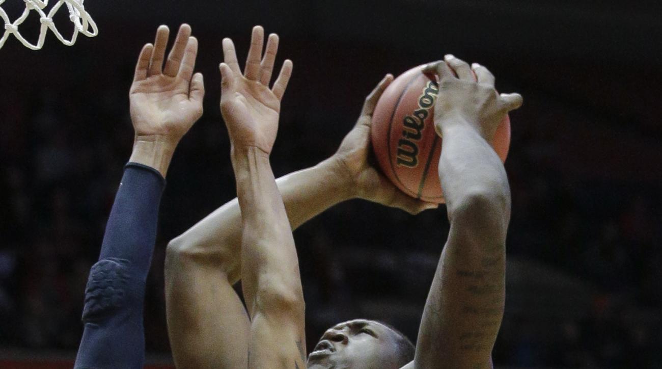 Cincinnati's Octavius Ellis (2) shoots against Morgan State's Rasean Simpson (3) in the first half of an NCAA college basketball game, Sunday, Dec. 6, 2015, in Cincinnati. (AP Photo/John Minchillo)
