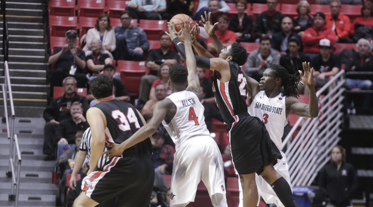 Biola's Terrell Funches tries to shoot before the shot clock expires while San Diego State's Dakarai Allen, left, and Angelo Chol defend in the first half of a NCAA basketball game, Monday, Dec. 7, 2015, in San Diego.  (AP Photo/Lenny Ignelzi)