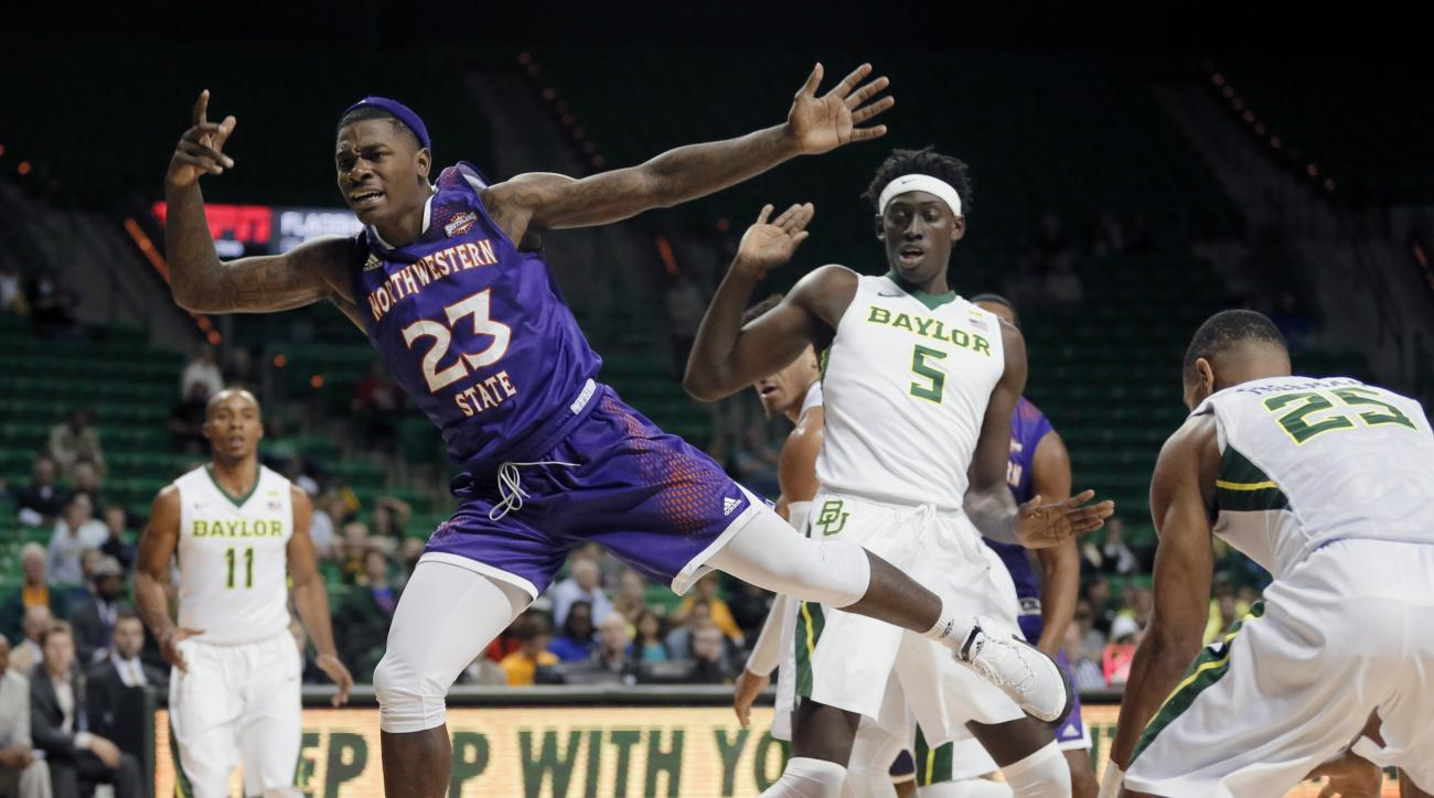 Northwestern State Demons's Zeek Woodley (23) is stripped of the ball on a drive to the basket on a combined effort by Baylor's Johnathan Motley (5) and Al Freeman (25) as Lester Medford (11) watches in the first half of an NCAA college basketball game, T