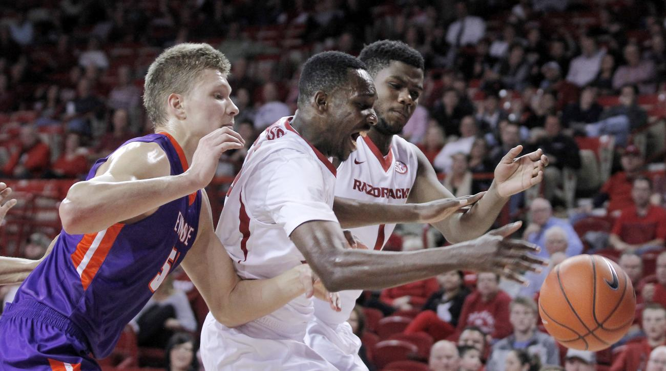 Evansville's Egidijus Mockevicius (55), from left, and Arkansas' Willy Kouassi (50) and Trey Thompson (1) go after a loose ball during the first half of an NCAA college basketball game, Tuesday, Dec. 8, 2015 in Fayetteville, Ark. (AP Photo/Samantha Baker)