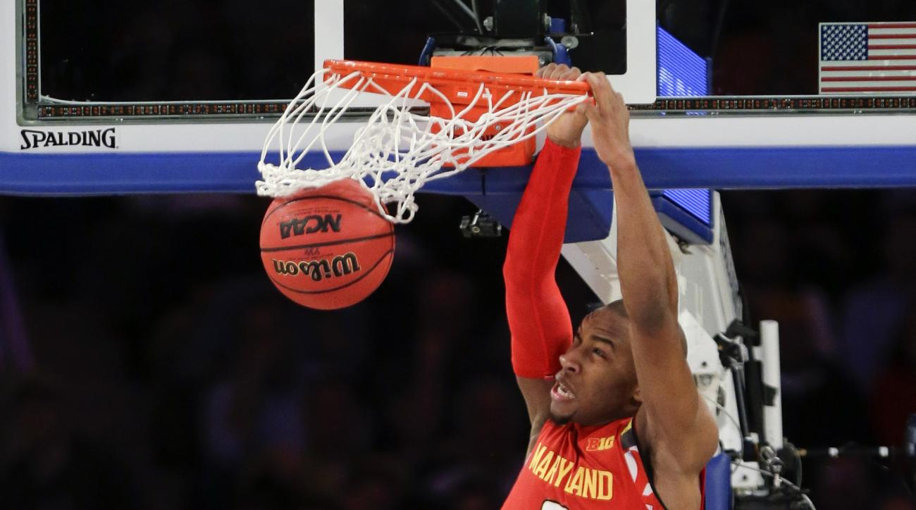 Maryland's Rasheed Sulaimon (0) dunks the ball in front of Connecticut's Steven Enoch (13) during the first half of an NCAA college basketball game Tuesday, Dec. 8, 2015, in New York. (AP Photo/Frank Franklin II)