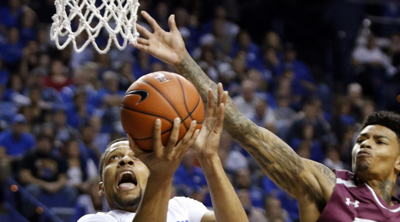 Kentucky's Isaiah Briscoe (13) shoots while defended by Eastern Kentucky's K.J. Bluford during the first half of an NCAA college basketball game Wednesday, Dec. 9, 2015, in Lexington, Ky. (AP Photo/James Crisp)
