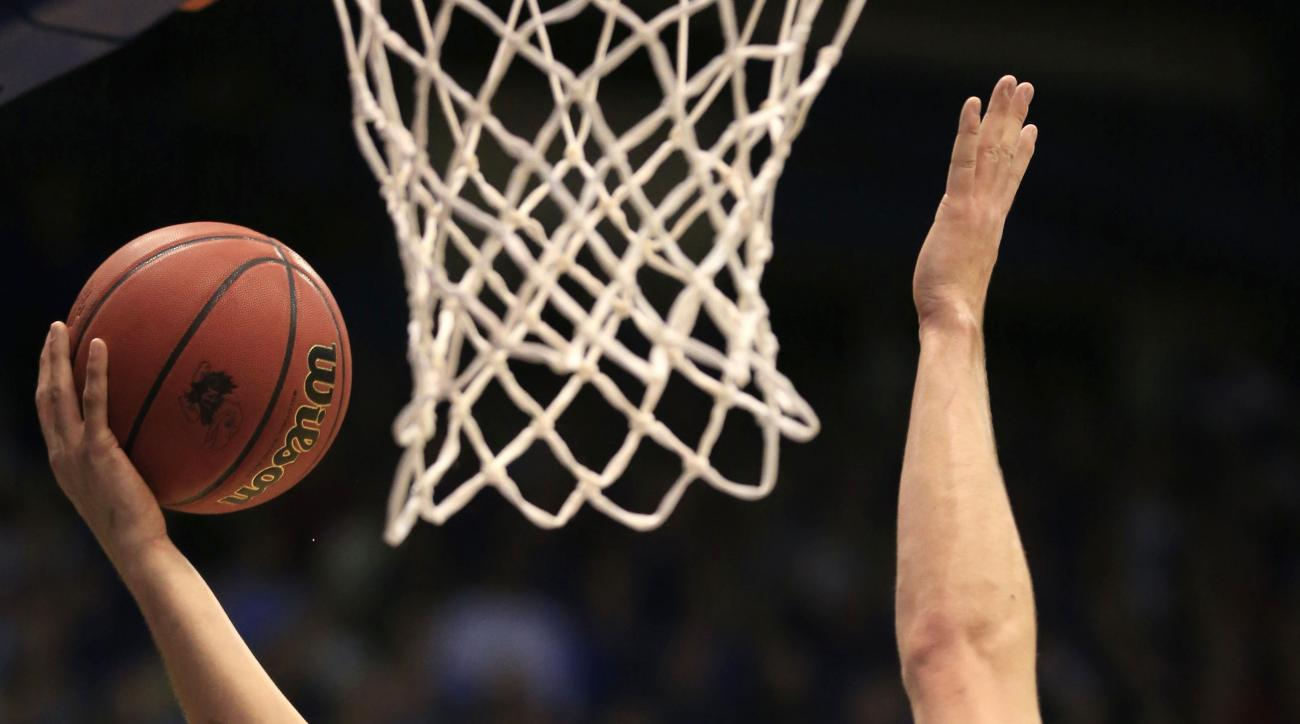 Kansas guard Brannen Greene (14) shoots while covered by Holy Cross center Matt Husek (42) during the first half of an NCAA college basketball game in Lawrence, Kan., Wednesday, Dec. 9, 2015. (AP Photo/Orlin Wagner)