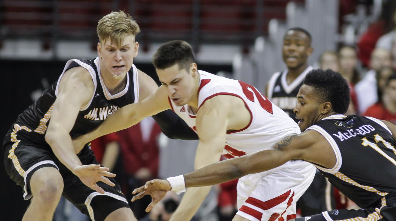 Milwaukee's Scotty Tyler, left, and JayQuan McCloud, right, battle for the ball against Wisconsin's Bronson Koenig (24) during the first half of an NCAA college basketball game Wednesday, Dec. 9, 2015, in Madison, Wis. (AP Photo/Andy Manis)