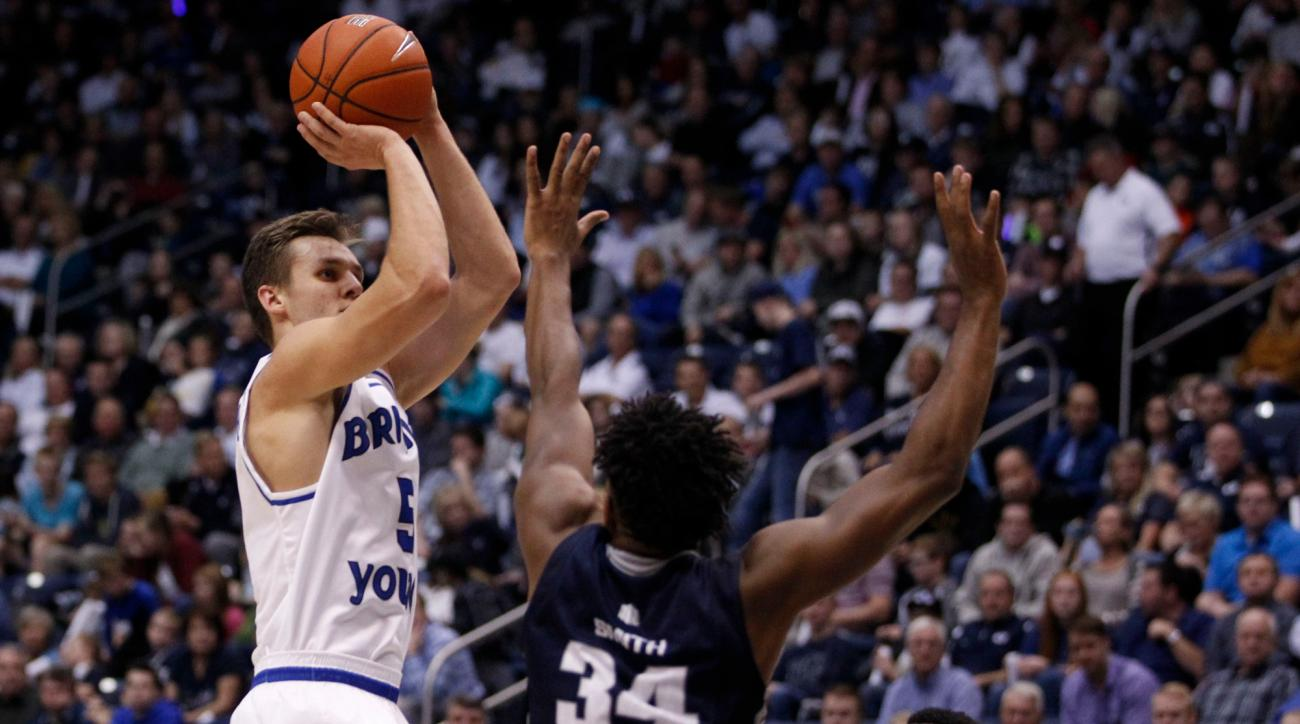 BYU guard Kyle Collinsworth (5) goes up for a shot while being guarded by Utah State guard Chris Smith (34) during an NCAA college basketball game, Wednesday, Dec. 9, 2015 in Provo, Utah. (Sammy Jo Hester/The Daily Herald via AP) MANDATORY CREDIT