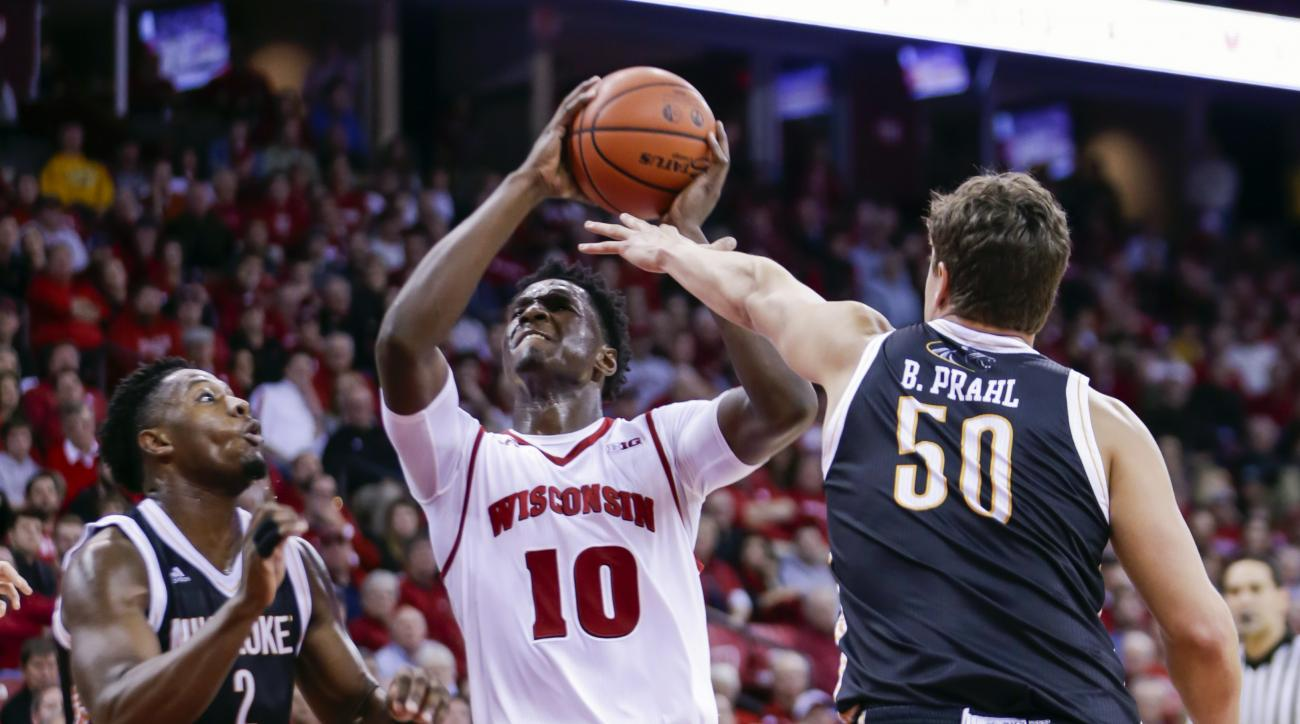 Wisconsin's Nigel Hayes (10) looks to shoot between Milwaukee's Akeem Springs (2) and Brett Prahl (50) during the second half of an NCAA college basketball game Wednesday, Dec. 9, 2015, in Madison, Wis. Milwaukee won 68-67. (AP Photo/Andy Manis)