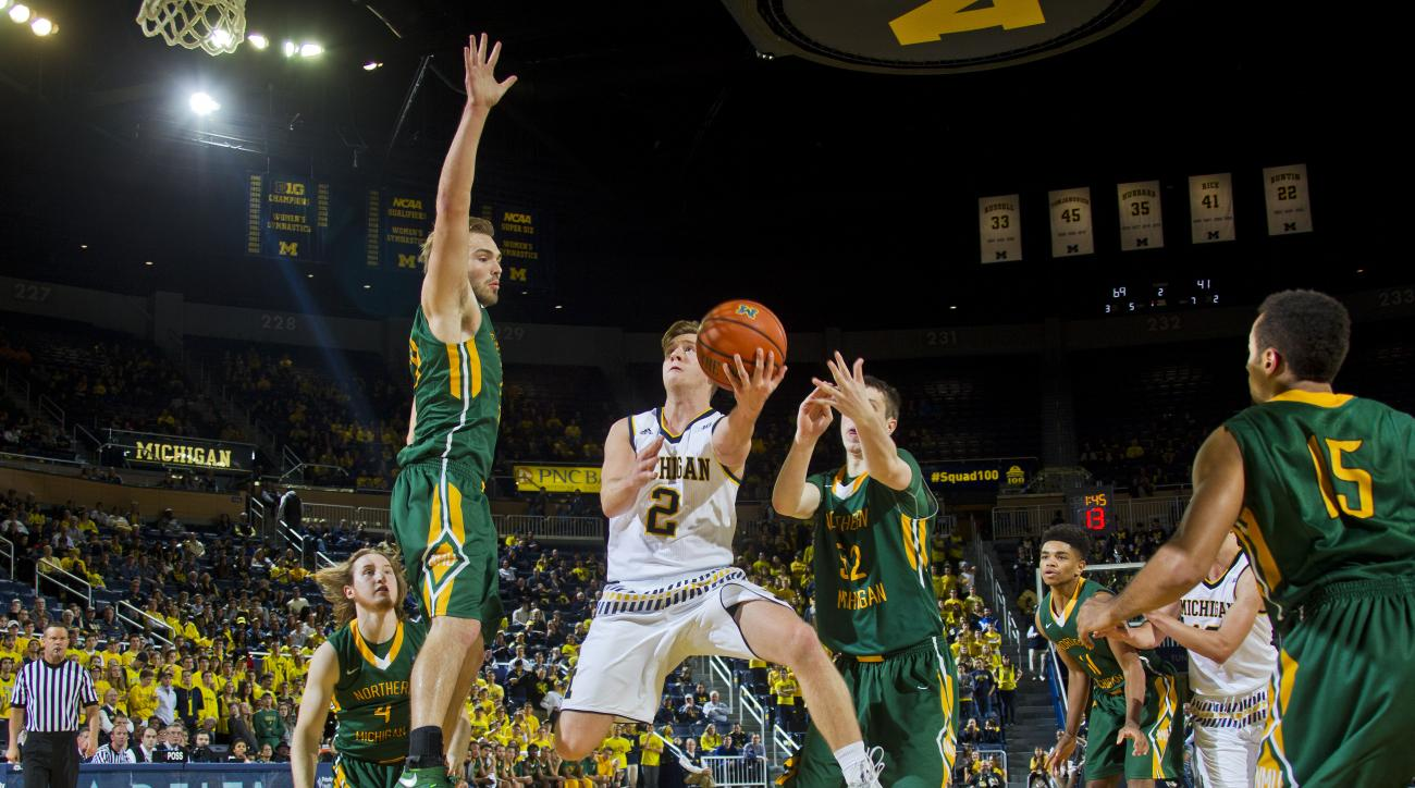 FILE - In this Nov. 13, 2015 file photo, Michigan guard Spike Albrecht (2) makes a layup between Northern Michigan forward Brett Branstrom, top left, and center Vejas Grazulis (52) in the second half of an NCAA college basketball game at Crisler Center in