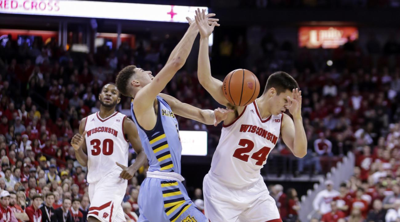 Wisconsin's Bronson Koenig (24) fouls Marquette's Sandy Cohen during the first half of an NCAA college basketball game Saturday, Dec. 12, 2015, in Madison, Wis. (AP Photo/Andy Manis)