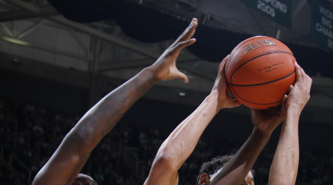 Florida's Dorian Finney-Smith (10) and Michigan State's Bryn Forbes battle for a rebound during the first half of an NCAA college basketball game, Saturday, Dec. 12, 2015, in East Lansing, Mich. (AP Photo/Al Goldis)