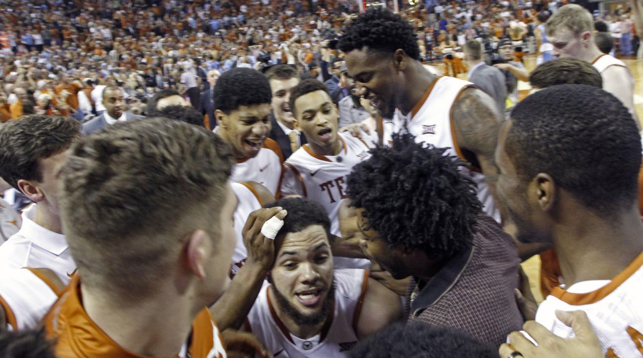 Texas guard Javan Felix, center, is swarmed by his teammate after making a last second shot during the second half of an NCAA college basketball game to defeat North Carolina, Saturday, Dec. 12, 2015, in Austin, Texas. Texas won 84-82. (AP Photo/Michael T