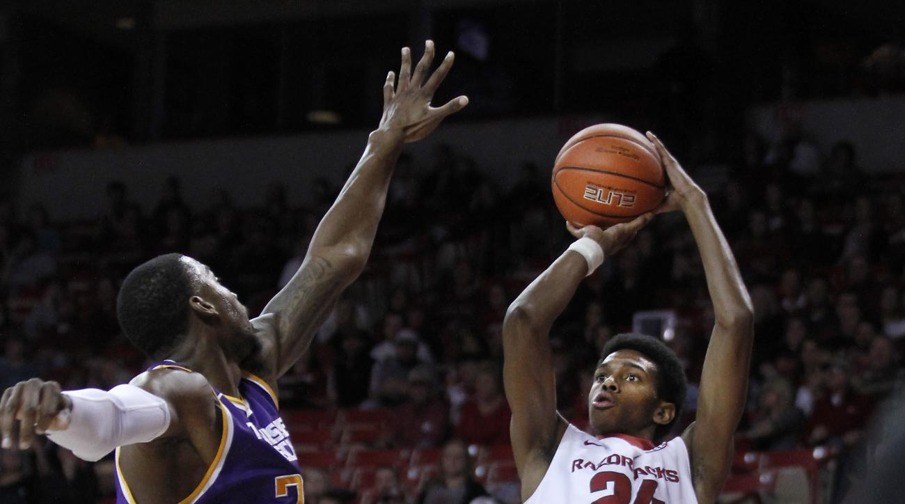 Arkansas' Jimmy Whitt (24) shoots from the outside despite Tennessee Tech's Anthony Morse's (35) attempt at a block during the first half of an NCAA college basketball game Saturday, Dec. 12, 2015, in Fayetteville, Ark. (AP Photo/Samantha Baker)