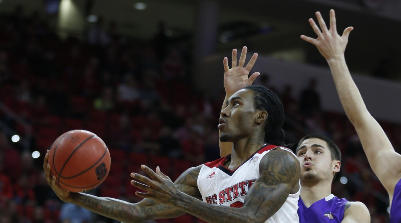North Carolina State's Cat Barber (12) drives to the basket past High Point's Lorenzo Cugini (15) during the first half of an NCAA college basketball game at PNC Arena in Raleigh, N.C., Wednesday, Dec. 16, 2015. (Ethan Hyman/The News & Observer via AP) MA