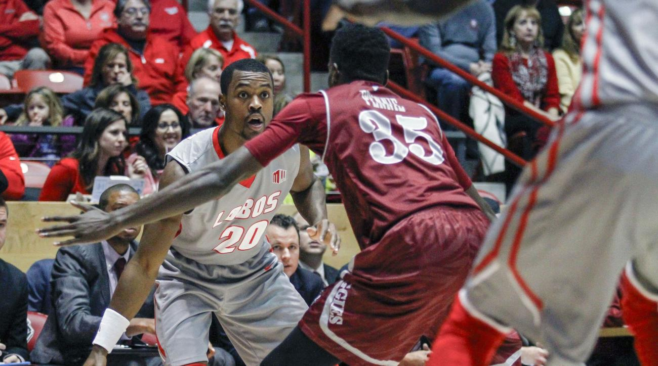 New Mexico's Sam Logwood (20) drives to the baseline guarded by New Mexico State's Jalyn Pennie (35) during the first half an NCAA college basketball game, Wednesday, Dec. 16, 2015, in Albuquerque, N.M. (AP Photo/Juan Labreche)