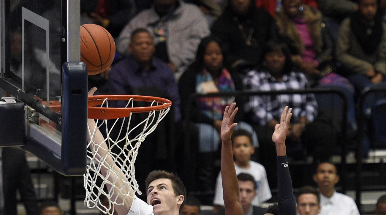 George Washington guard Matt Hart (30) goes to the basket against St. Peter's guard Antwon Portley (13) during the first half of an NCAA college basketball game, Saturday, Dec. 19, 2015, in Washington. (AP Photo/Nick Wass)