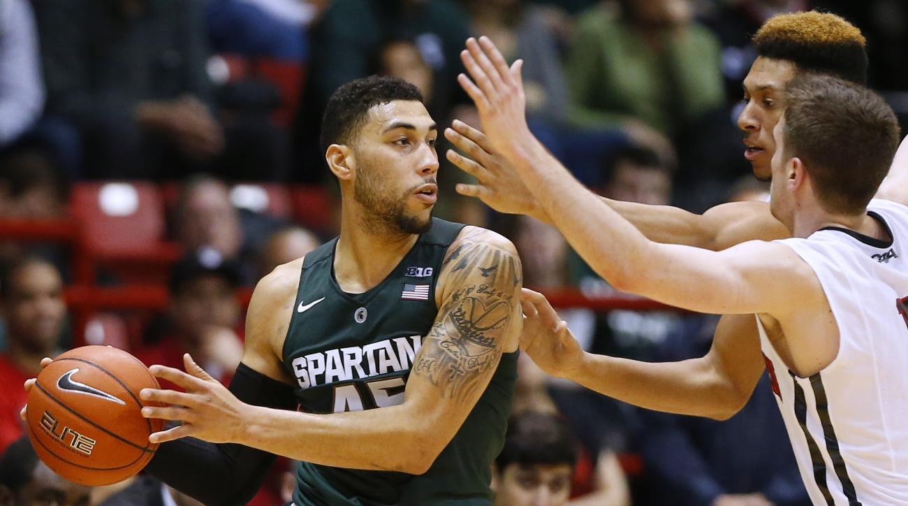 Michigan State's Denzel Valentine looks for an opening around Northeastern's Caleb Donnelly and Jeremy Miller, rear, during the second half of Michigan State's 78-58 win over Northeastern in an NCAA college basketball game in Boston Saturday, Dec. 19, 201
