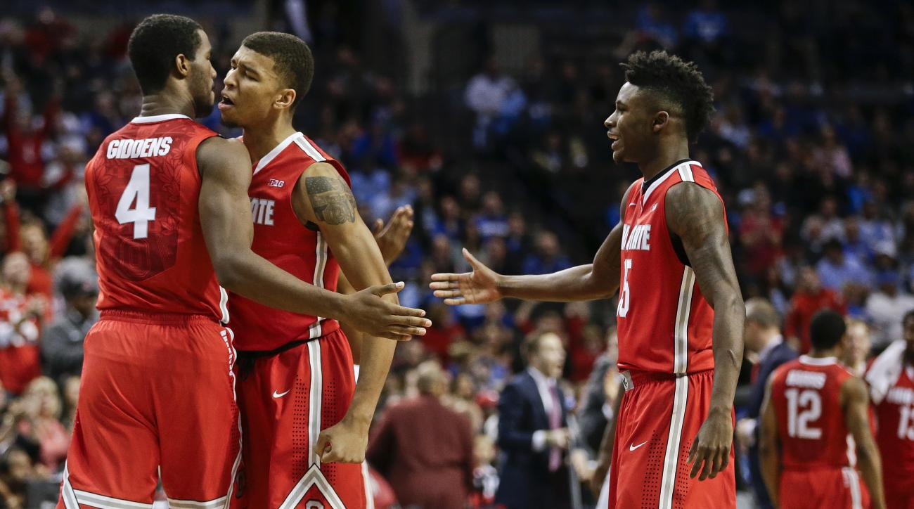 Ohio State's Daniel Giddens (4) and Marc Loving (2) celebrate as Kam Williams (15) walks toward them during the second half of an NCAA college basketball game against Kentucky Saturday, Dec. 19, 2015, in New York. Ohio State won 74-67. (AP Photo/Frank Fra