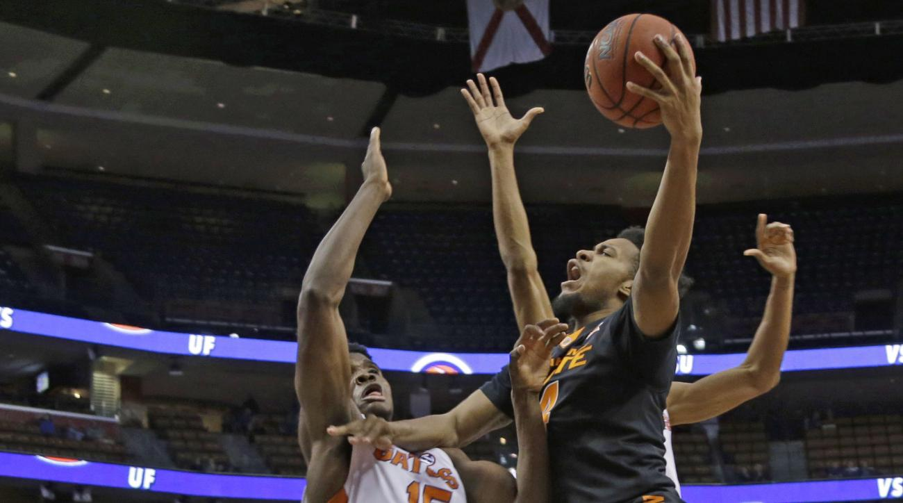 Oklahoma State's Joe Burton, right, drives to the basket as Florida 's John Egbunu (15) defends in the first half of the NCAA college Orange Bowl Basketball Classic, Saturday, Dec. 19, 2015, in Sunrise, Fla. (AP Photo/Lynne Sladky)