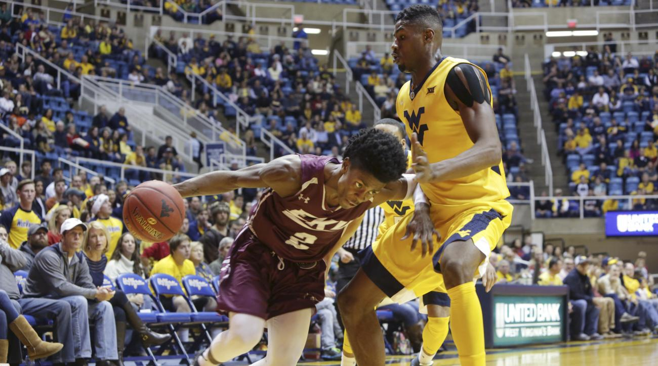 West Virginia forward Jonathan Holton (1) tries to trap Eastern Kentucky guard Paul Jackson (2) during the first half of an NCAA college basketball game Monday, Dec, 21, 2015, in Morgantown, W.Va. (AP Photo/Raymond Thompson)