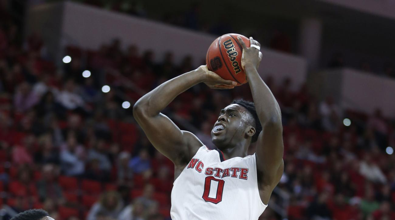 North Carolina State's Abdul-Malik Abu (0) shoots as UNC Greensboro's Kayel Locke (13) looks on during the first half of an NCAA college basketball game, Tuesday, Dec. 22, 2015 in Raleigh, N.C. (Ethan Hyman/News & Record via AP) MANDATORY CREDIT