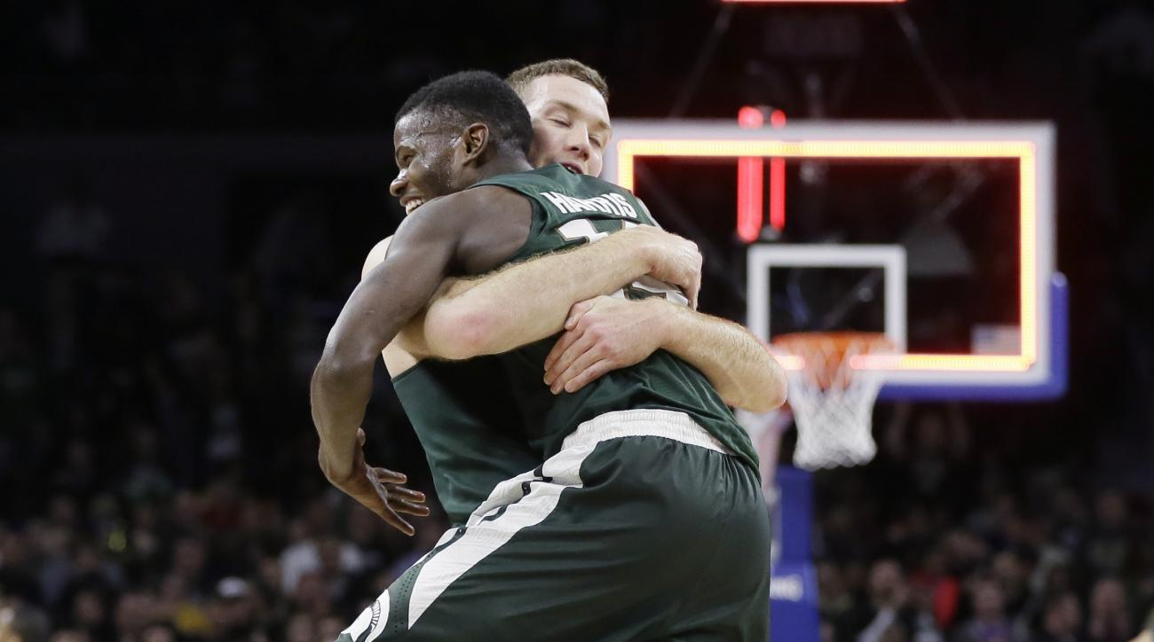 Michigan State forward Matt Costello, rear, hugs guard Eron Harris after overtime of an NCAA college basketball game against Oakland, Tuesday, Dec. 22, 2015, in Auburn Hills, Mich. Michigan State defeated Oakland 99-93. (AP Photo/Carlos Osorio)