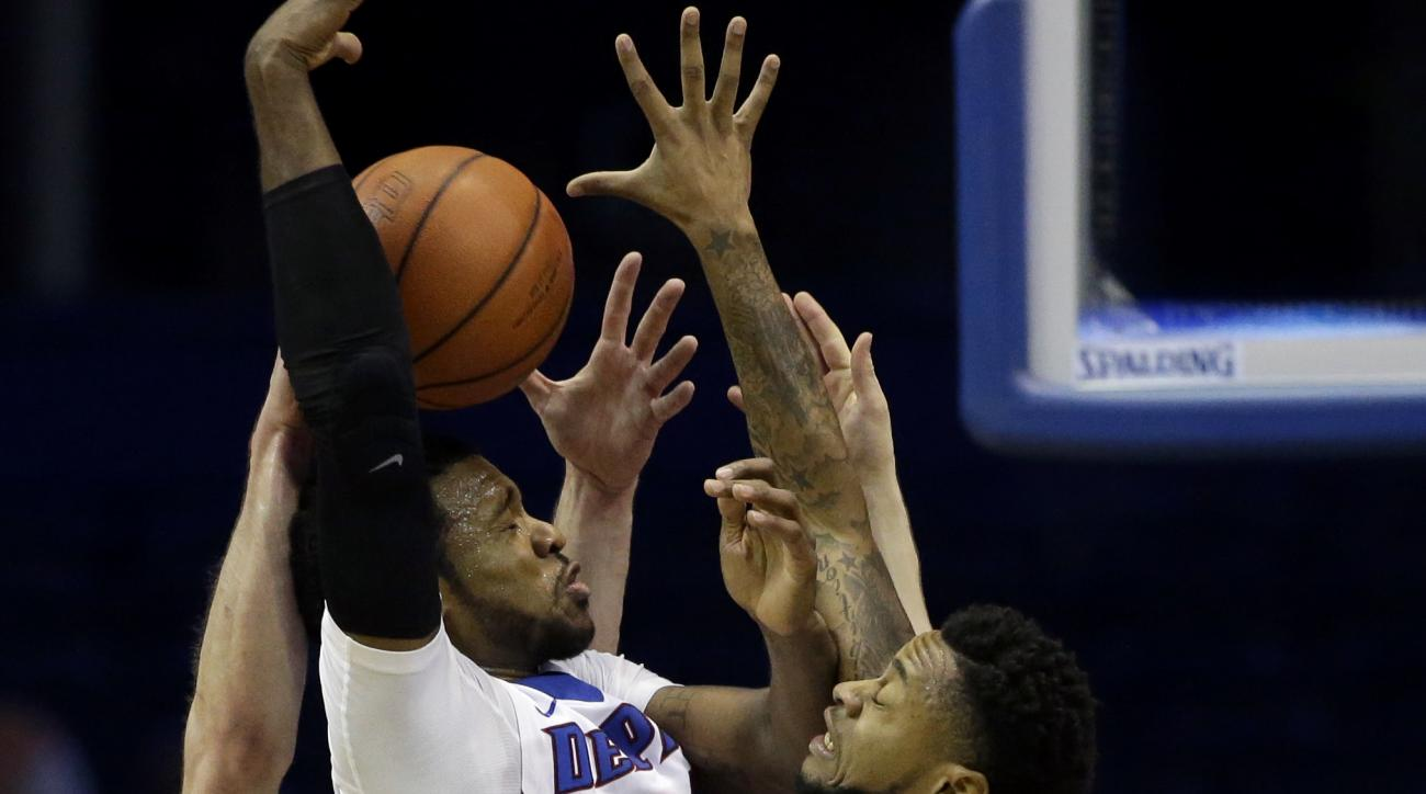 DePaul forward Myke Henry, second from left, guard Aaron Simpson, second from right, battle for a rebound against George Washington forward Tyler Cavanaugh, left, and guard Paul Jorgensen during the first half of an NCAA college basketball game on Tuesday