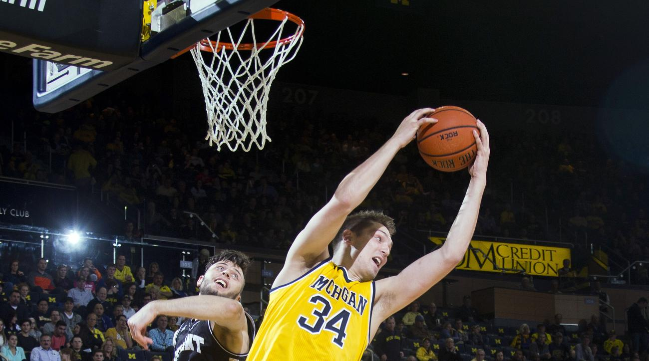 Michigan forward Mark Donnal (34) beats Bryant guard Bosko Kostur, left, to a rebound during the first half of an NCAA college basketball game in Ann Arbor, Mich., Wednesday, Dec. 23, 2015. (AP Photo/Tony Ding)