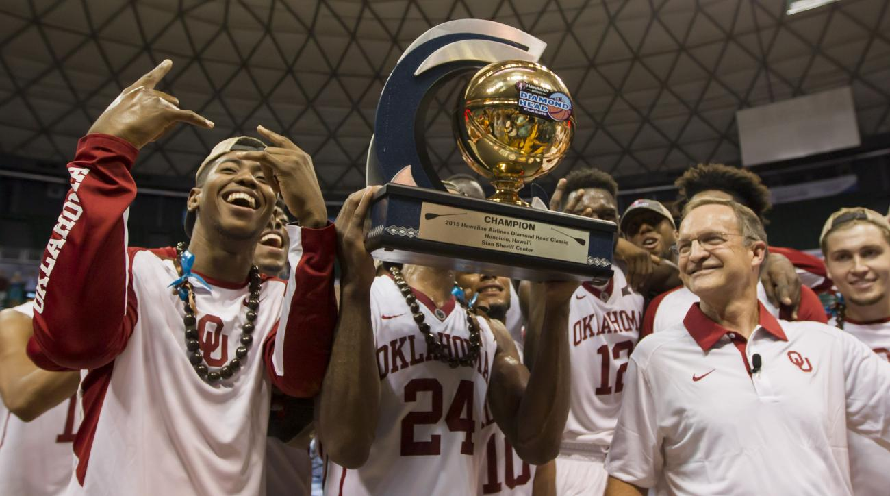 Oklahoma head coach Lon Kruger, right, smiles and looks on as his team poses for a picture with the Diamond Head Classic championship trophy after an NCAA college basketball game against Harvard, Friday, Dec. 25, 2015, in Honolulu. Oklahoma won 83-71. (AP