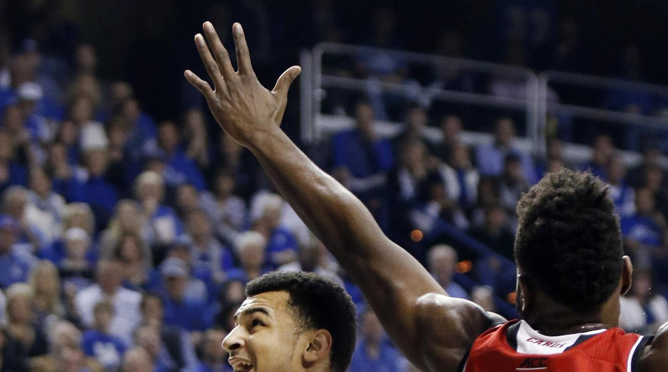 Kentucky's Jamal Murray, left, looks for an opening on Louisville's Chinanu Onuaku (32) during the first half of an NCAA college basketball game Saturday, Dec. 26, 2015, in Lexington, Ky. (AP Photo/James Crisp)
