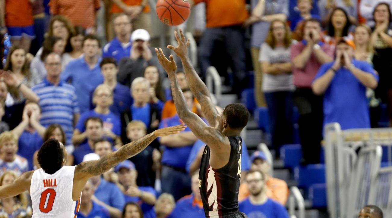 Florida State guard Dwayne Bacon (4) makes the game-winning shot over Florida Gators guard Kasey Hill (0) during the second half of an NCAA college basketball game Tuesday, Dec. 29, 2015, in Gainesville, Fla. Florida State won 73-71. (Matt StameyThe Gaine
